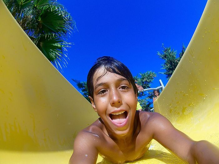 Close-up portrait of cheerful shirtless boy sliding on water slide
