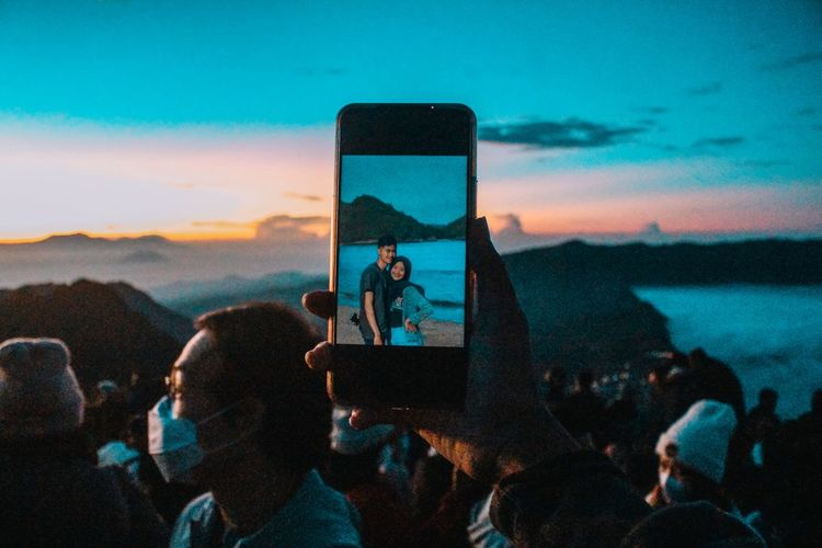 People photographing against sky during sunset