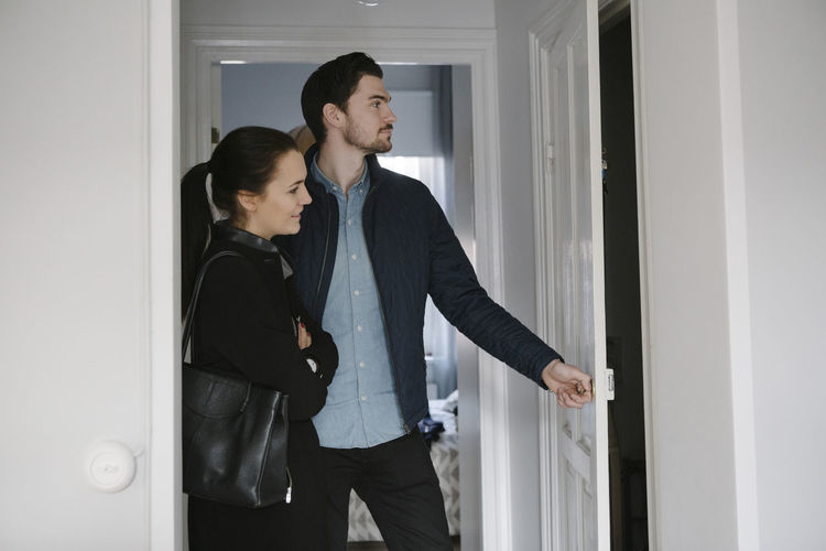 Side view of young couple looking at entrance