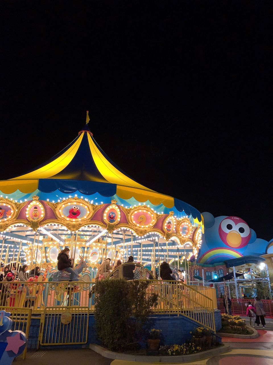 arts culture and entertainment, night, amusement park, amusement park ride, carousel, illuminated, sky, representation, animal representation, incidental people, copy space, built structure, architecture, lighting equipment, outdoors, carousel horses, nature, glowing, merry-go-round, fairground