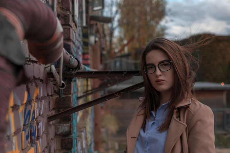Portrait of young woman wearing eyeglasses while standing by wall