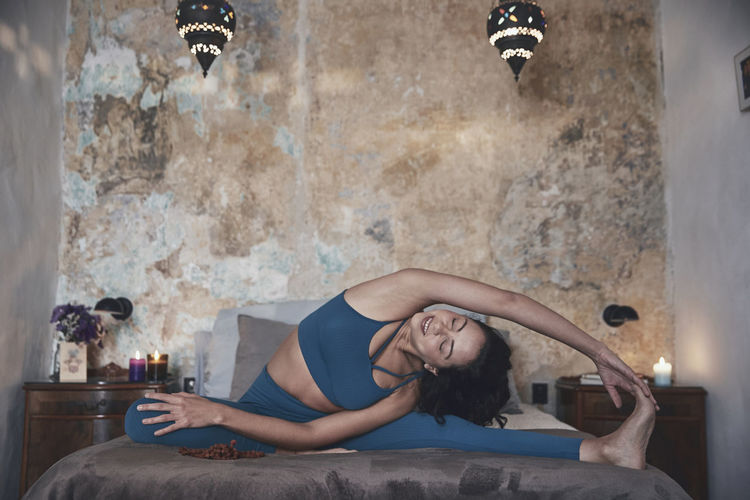 Woman exercising while sitting on bed against wall at home