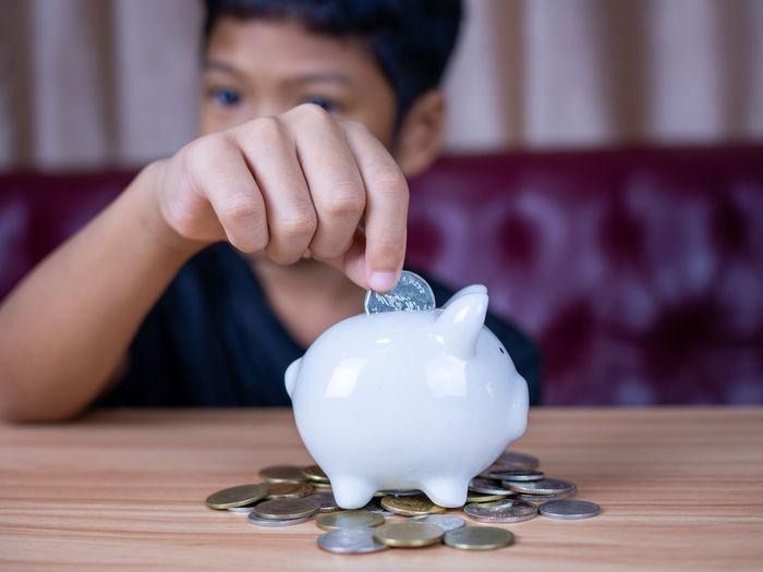 Boy saving money in a white pig piggy bank.saving concept. saving for the future.