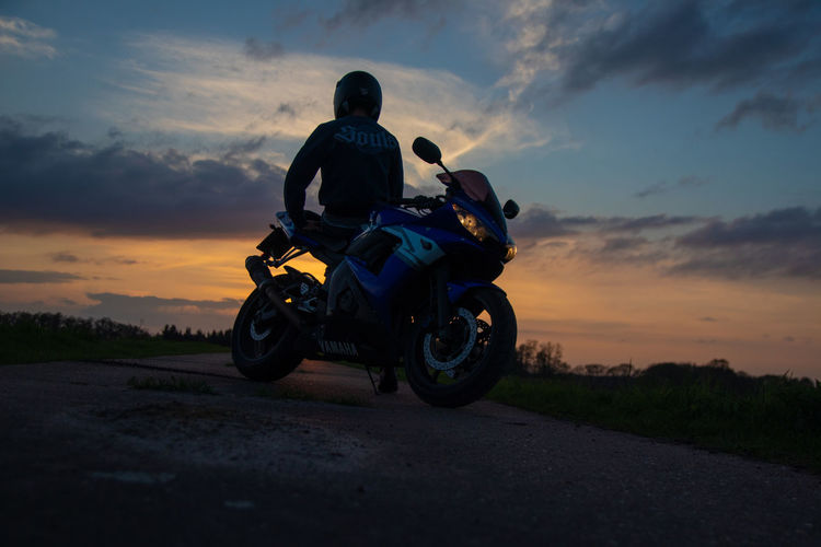 Man riding motorcycle on road against sky during sunset