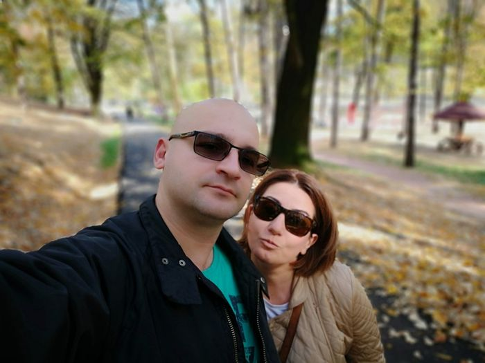 Portrait of couple standing on road during autumn