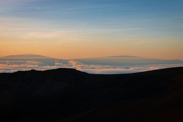 Peak of mauna kea, big island seen from haleakala on maui, hawaii, usa at sunrise against sky