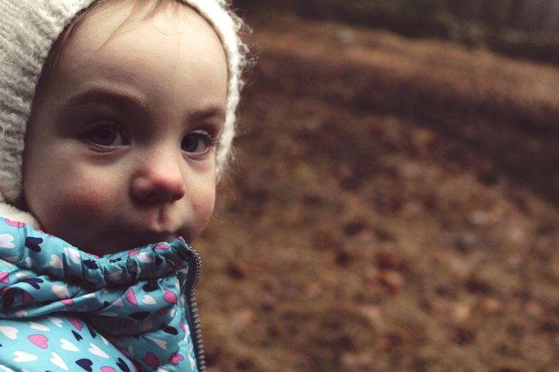Close-up portrait of cute baby girl in warm clothing