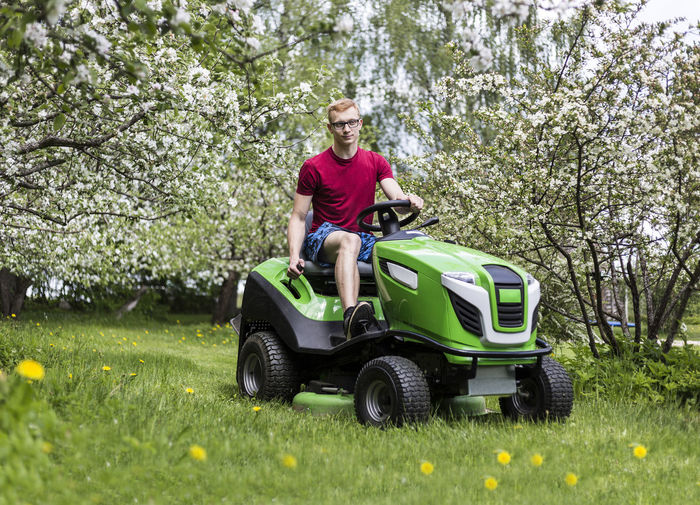 Young man, gardener driving ride on mower. Mowing grass in yard, tractor. Gardening. Apple Tree Backyard Blooming Countryside Garden Gardener Grass Grass Cutter Grass Cutting. Lawn Lawn Mowing Lawnmower Man Mowing Mowing Tractor Nature Nature One Person People Real People Riding Mower Spring Tractor Tree Trees