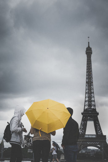 Low angle view of people by eiffel tower against cloudy sky