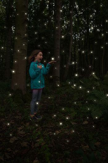Full length of woman standing on illuminated tree at night