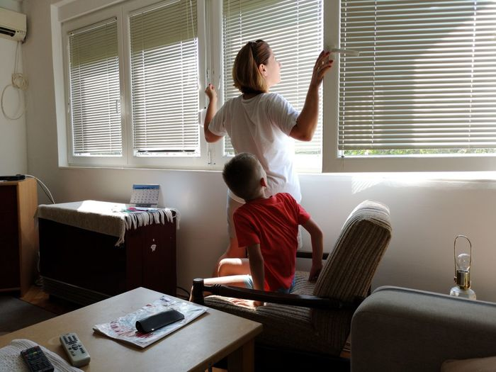 Mother and son looking through window at home