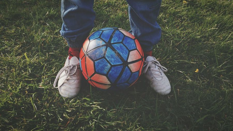 Low section of man with soccer ball on grassy field