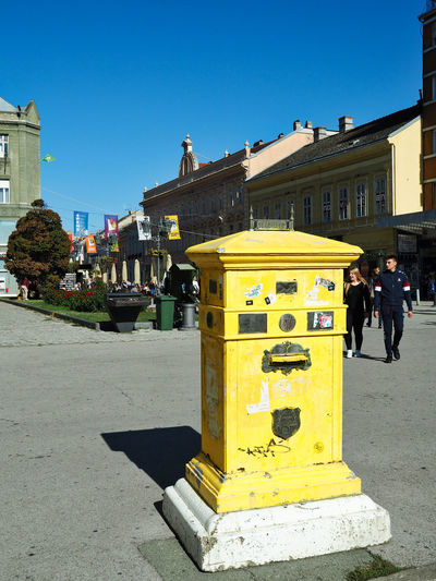 European Cities Novi Sad Serbia Eastern Europe Balkans Europe Outdoors Public Places Leisure Activity Pedestrian Walkway Building Exterior Architecture Built Structure Building City Real People Day Street Yellow Sunlight Incidental People Communication Shadow Mailboxes