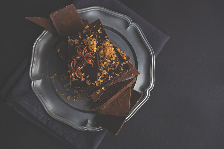 Close-up of chocolate bars with star anise in plate on table