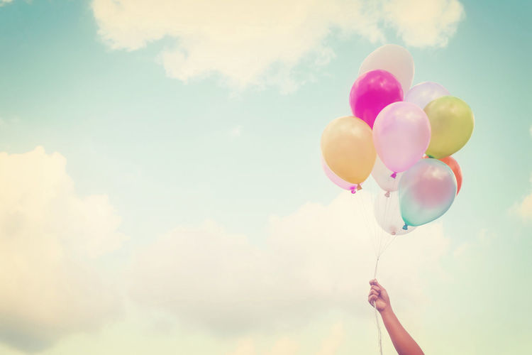 Girl hand holding multicolored balloons done with a retro vintage instagram filter effect, concept of happy birth day in summer and wedding honeymoon party (Vintage color tone) Balloon Holding Human Hand Multi Colored Helium Balloon Outdoors Summer Celebration Cloud - Sky Holiday Vintage Honeymoon Birthday Pink Color