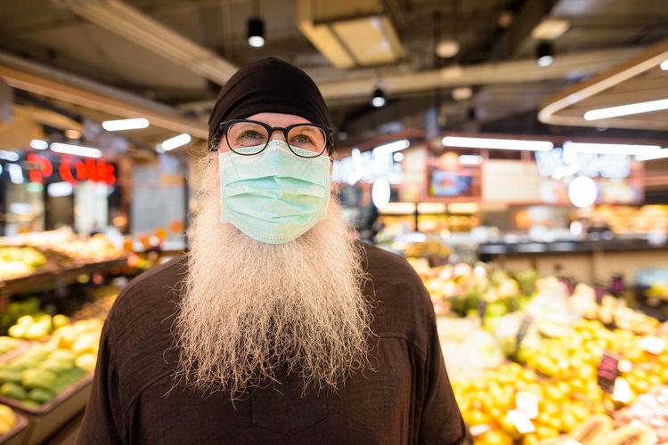 Portrait of man wearing mask in store
