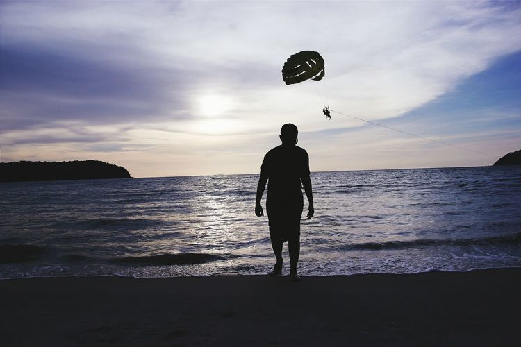 Silhouette man at beach with people parasailing over sea against sky