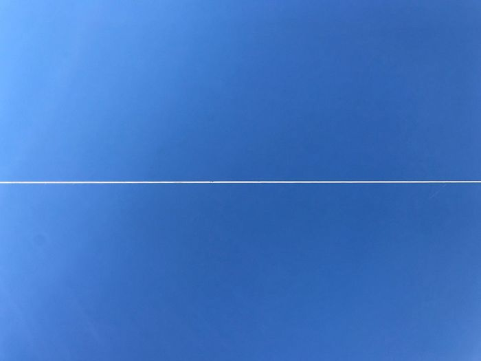 Vapor trail against clear blue sky