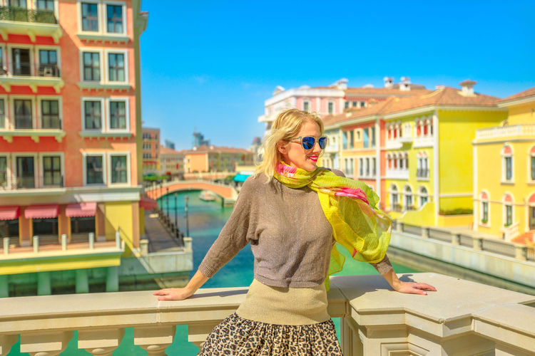 Carefree woman on balcony overlooking canals of Venice, a Venetian style waterfront village. Caucasian happy tourist enjoys Qanat Quartier in The Pearl-Qatar, icon of Doha, Persian Gulf, Middle East. Doha Doha,Qatar Qatar Arab Arabic Arabian Venezia Venice Venice, Italy Venice Canals Canal Bridge Woman Females Tourism Tourist People Model Sunset City Town The Pearl, Doha Qanat Al Qasba Girl Venetian Architecture Building Exterior Built Structure Blond Hair Hair One Person Women Standing Hairstyle Building Fashion Adult Casual Clothing Day Lifestyles Nature Young Adult Beautiful Woman Outdoors