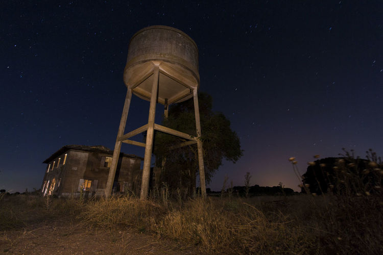 Abandoned Architecture Astronomy Building Exterior Built Structure Field Land Low Angle View Nature Night No People Outdoors Plant Sky Space Star - Space Storage Tank Tower Tree Water Conservation Water Tower - Storage Tank