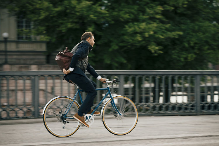 Full length of man riding bicycle on city