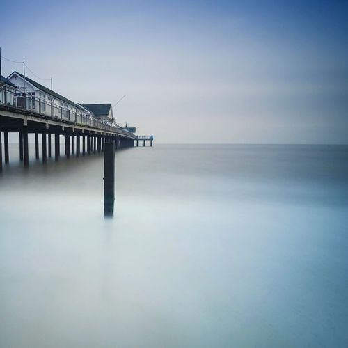 Scenic view of pier on sea against sky during misty morning