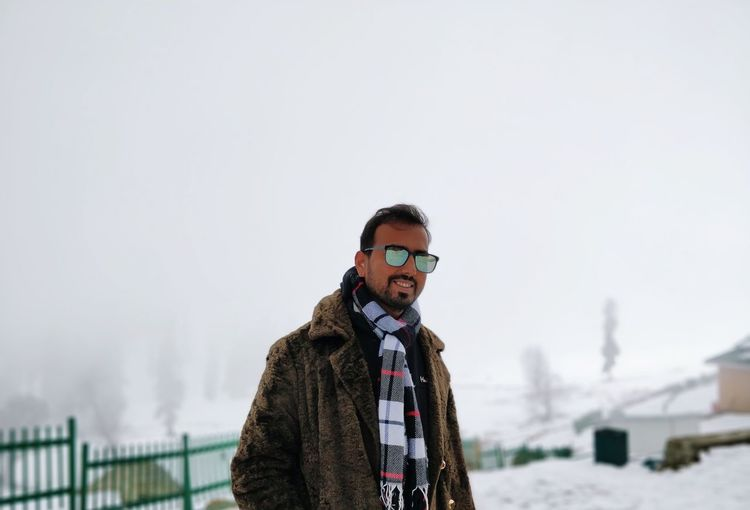 Portrait of young man in warm clothing wearing sunglasses while standing on snow against sky