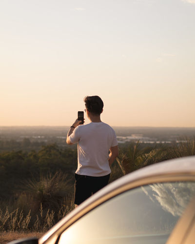 Full length of man photographing on mobile phone against sky
