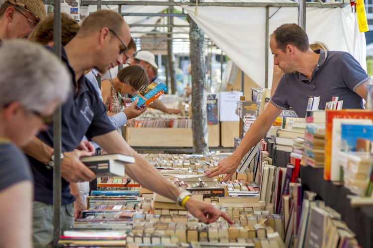 Choosing the right book Books EventPhotography Read Second Hand Street Market Book Bookmarket Cheap Dutch Education Educational Information Outside Outside Photography Paperback Paperback Novel People People And Places Publication Reading A Book Real People Streetphotography Sunny Day Urban Vintage