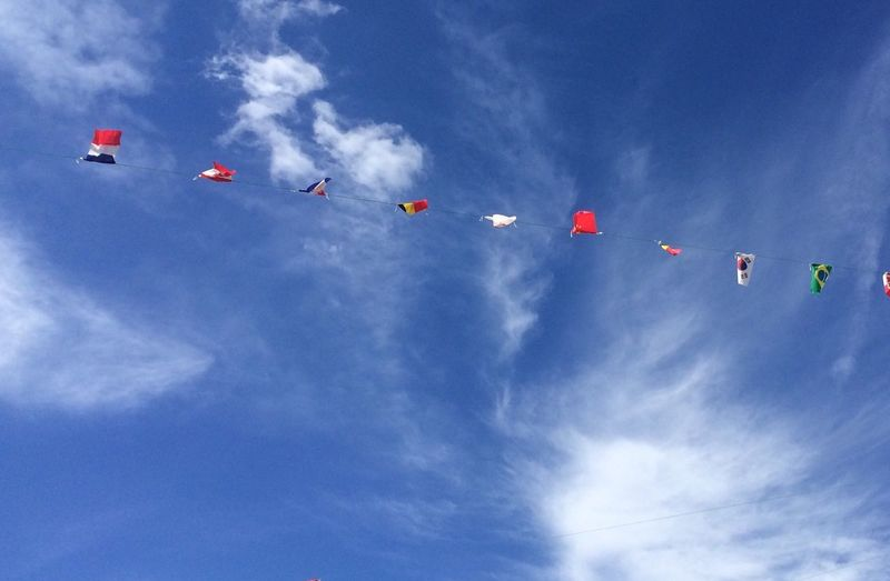 Low angle view of nation flags hanging against sky