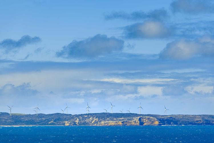 Windmills by sea against sky