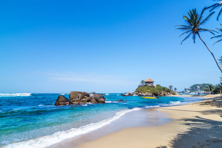 Scenic View Of Beach And Sea Against Blue Sky At Tayrona National Park
