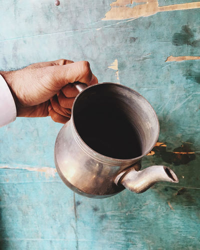 Cropped hand of man holding vintage kettle by weathered blue wall