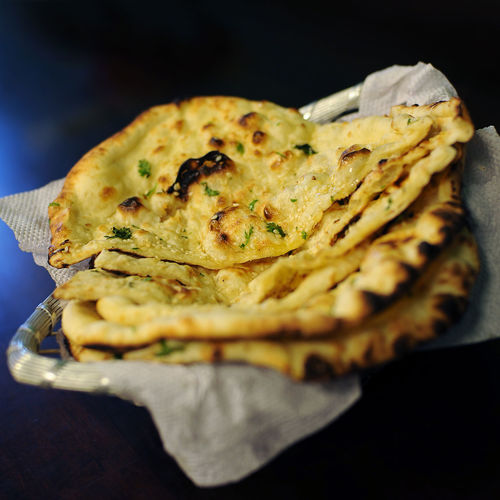 Close-up of butter naans in container