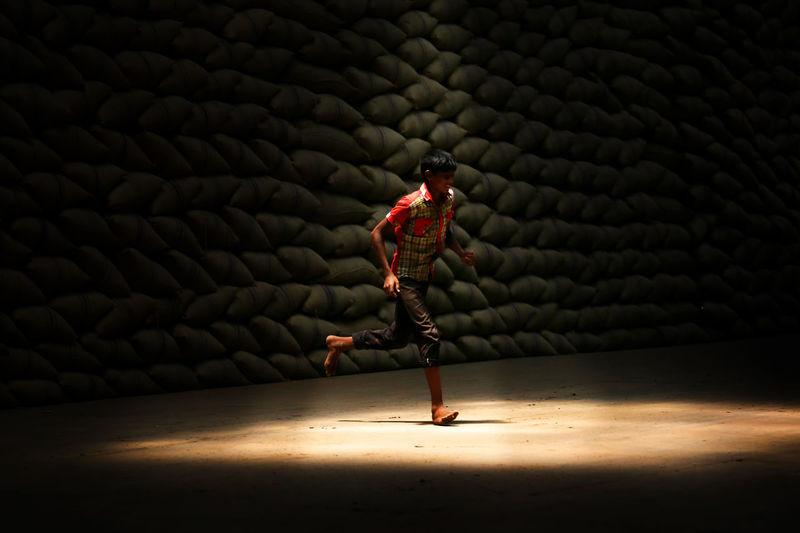 Teenage boy running on floor in sunlight against heap of sacks at storage room