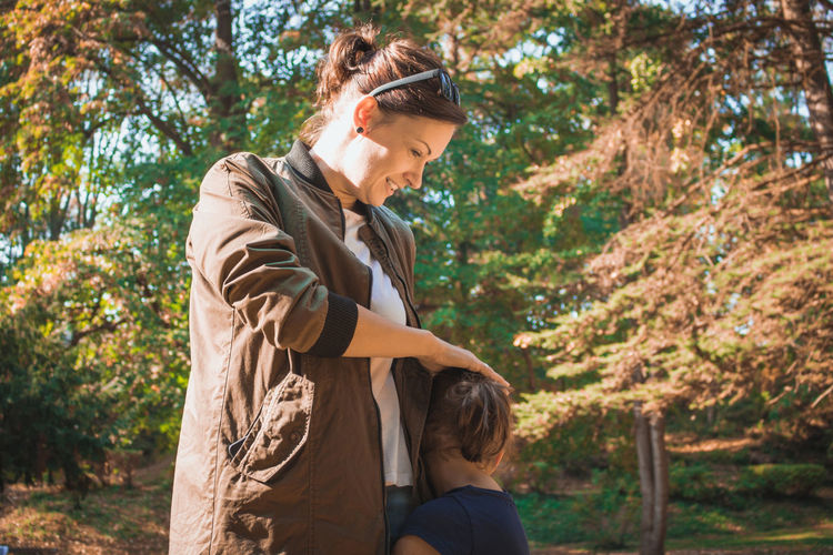 Side view of girl embracing smiling mother in park during autumn