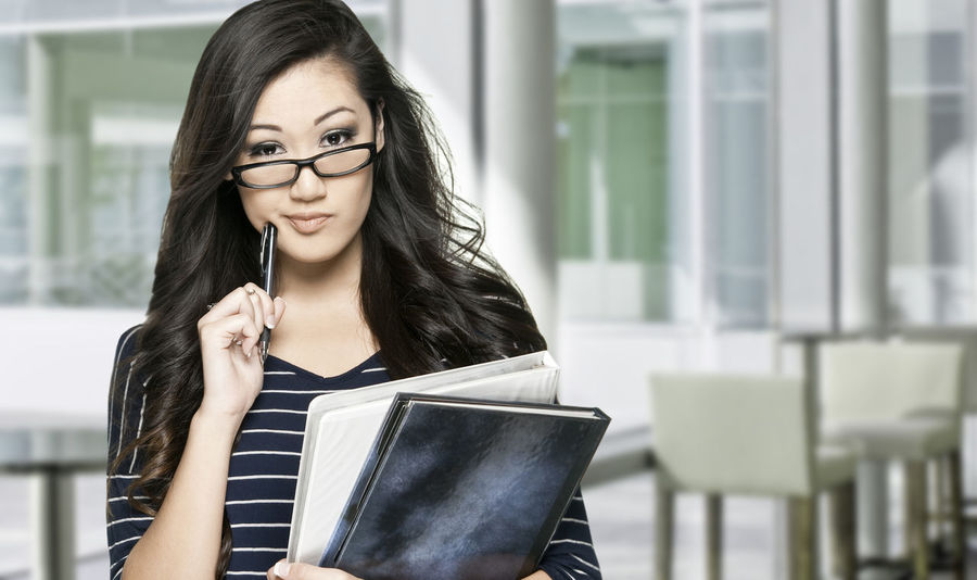 female student Asian Girl Books Contemplating Contemplation Decision Education Expression Female Girl Glasses Holding Indoors  Learning Lifestyles Person Selective Focus Student Young Adult Young Women