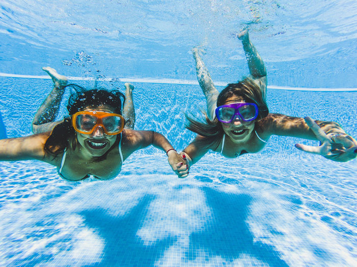 Portrait of happy female friends swimming in pool