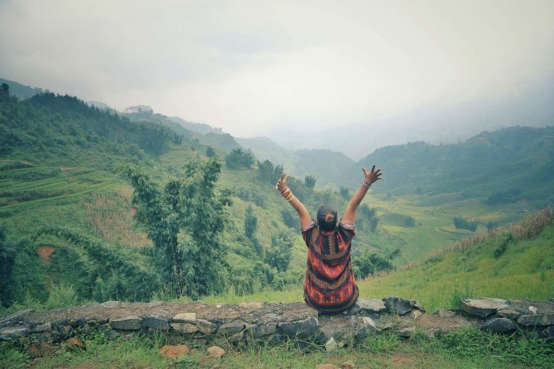 Rear View Of Woman With Arms Raised Sitting Against Mountains