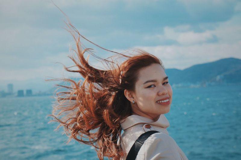 Portrait of happy woman against sea against sky