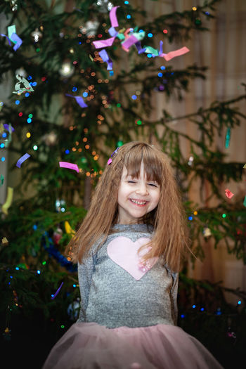 Portrait of happy girl with christmas tree