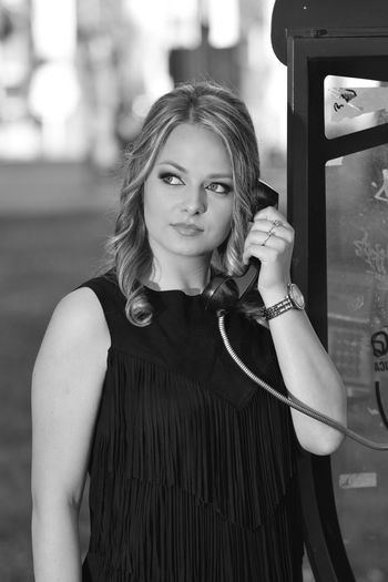 Portrait of young woman standing outdoors by the telephone booth