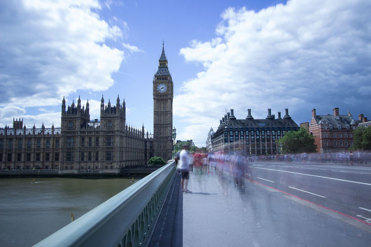 Blurred motion of people on westminster bridge against cloudy sky