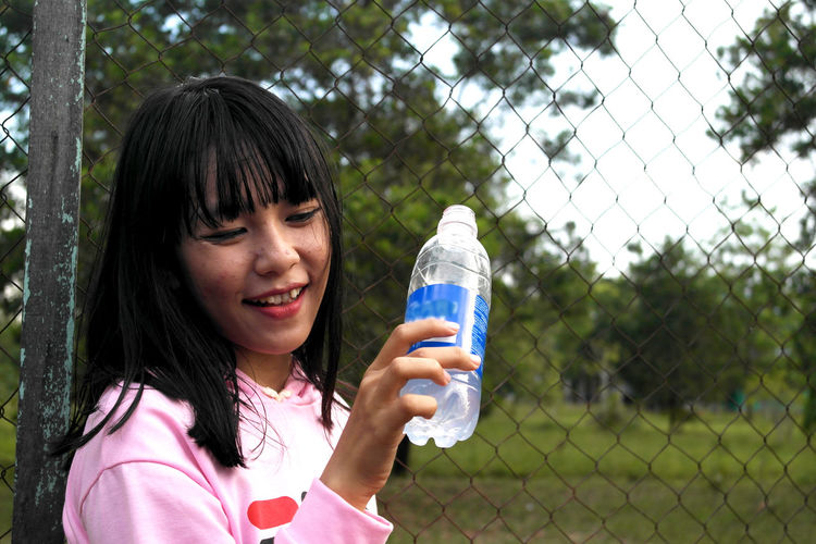 Smiling woman holding water bottle