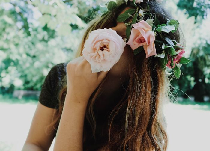 Close-up portrait of young woman wearing flowers outdoors