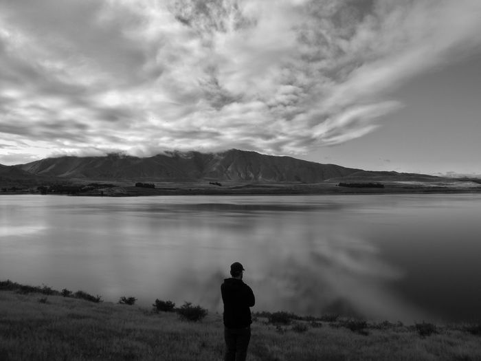 Rear view of silhouette man standing by lake against cloudy sky