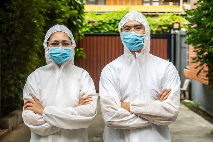 Portrait of man and woman wearing protective suit with mask standing outdoors