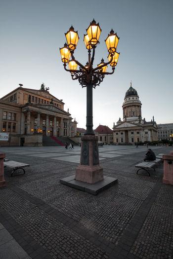 Illuminated street light by building against sky