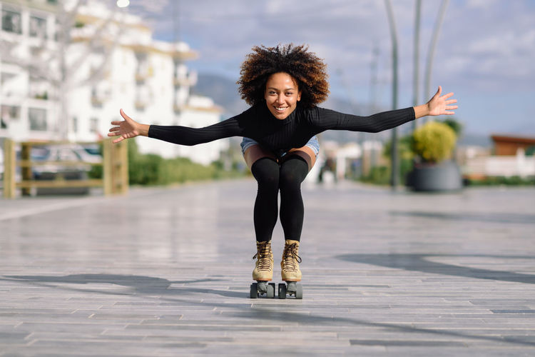 Portrait of smiling woman with arms outstretched roller skating on footpath in city