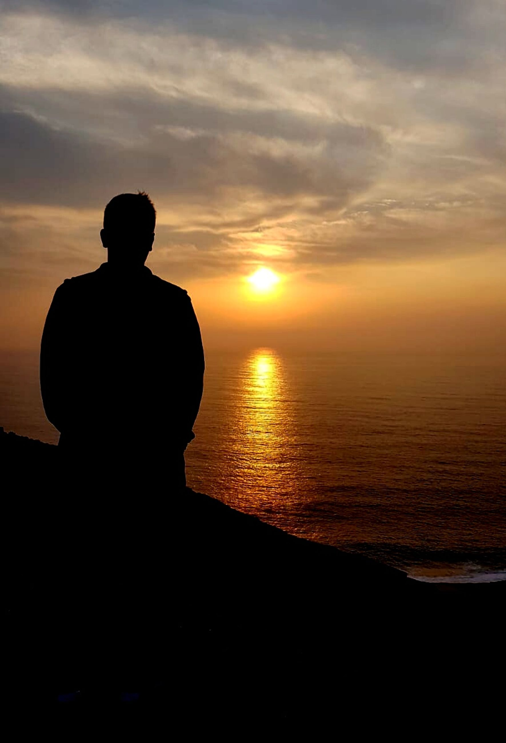 sunset, silhouette, sky, water, one person, leisure activity, real people, scenics - nature, tranquility, beauty in nature, sea, tranquil scene, orange color, lifestyles, men, nature, cloud - sky, sitting, beach, horizon over water